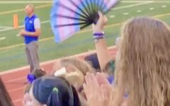 A student waves a fan sporting the trans pride flag in the student section of Powderpuff